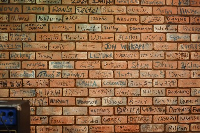 The back wall is made up of bricks, signed by those who have taken stage at B Flat.